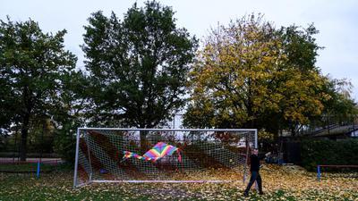 Den verwaisten Fussballplatz der SG Rueppurr nutzt ein Passant zum Drachensteigen.  GES/ Fussball/ Sport waehrend Corona, 01.11.2020  Sport during the Corona Crisis, November 1, 2020