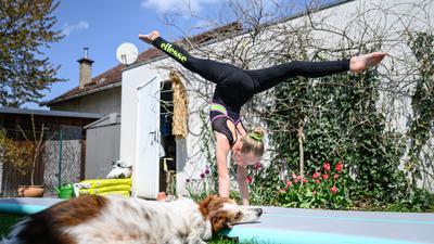 Jette Schroeder (KRK) trainiert im Garten des elterlichen Hauses auf einer AirTrack Matte. Hund Sally schaut zu.  GES/ Turnen/ Home-Training in Corona-Zeiten. 21.4.2021