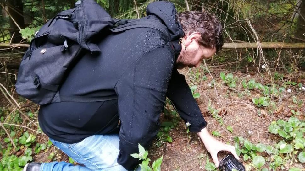 Geocaching Anfänger kniet vor einem Cache.