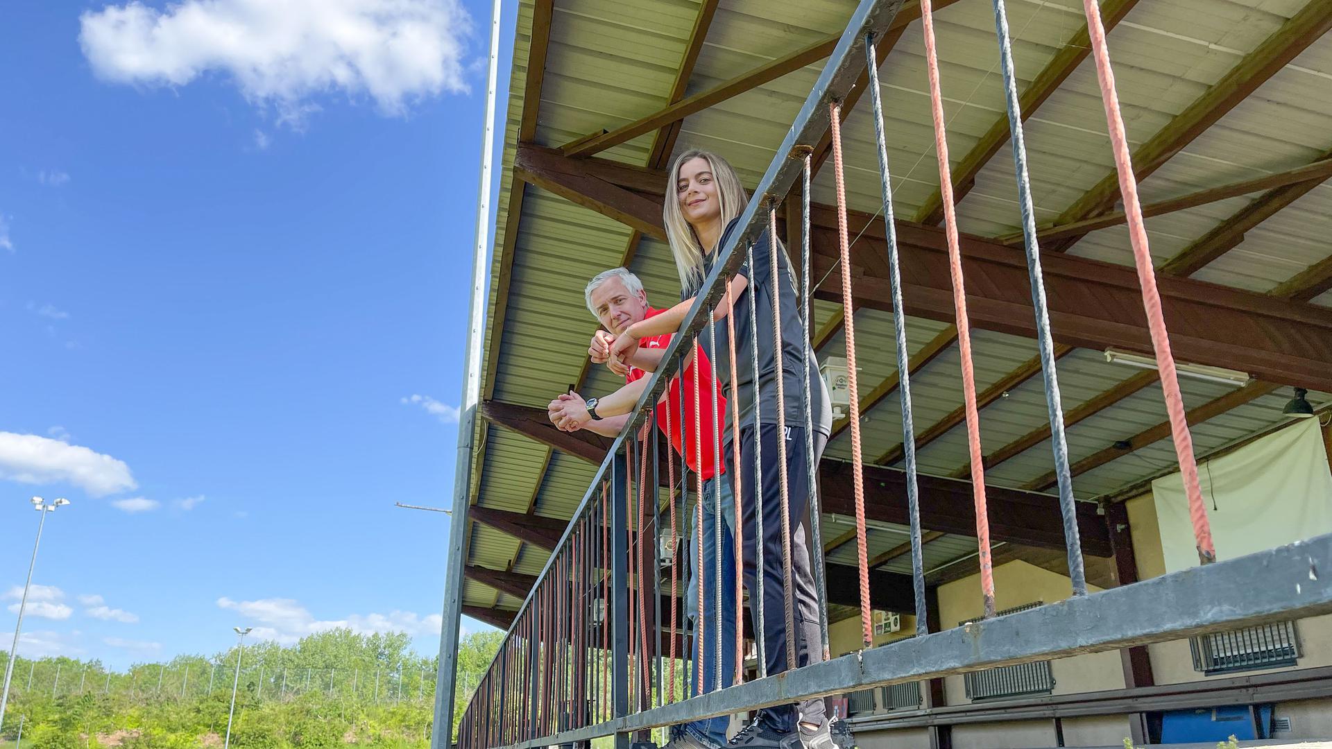 Mirko Just und Ramona Lechner vom FSV Büchenau stehen auf der Tribüne des Sportplatzes. Der Verein sammelt gerade für die Erneuerung des Geländers.