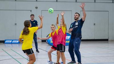 Kreisläufer Jannik Kohlbacher (rechts) hat sichtlich Spaß am Training mit den Jungs und Mädchen des Löwen-Handball-Camps beim TSV Rintheim.