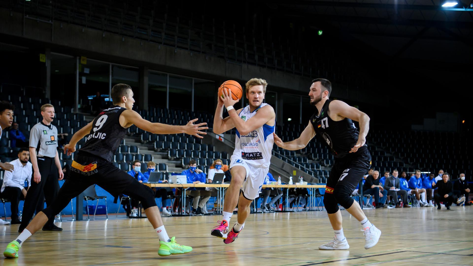 Aleksa Bulajic (Kirchheim), Antonio Pilipovic (Lions) im Zweikampf mit Andreas Kronhardt (Kirchheim) (von links).  GES/ Basketball/ ProA: PSK Lions - VfL Kirchheim Knights, 14.11.2020 --