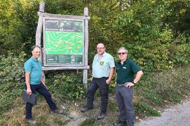 Der Vorsitzende des RSV Edelweiß Kartung Lothar Walter, Forst-Bezirksamtsleiter Clemens Erbacher und Revierförster Georg Schumann vor Schild des Trails in Sinzheim.