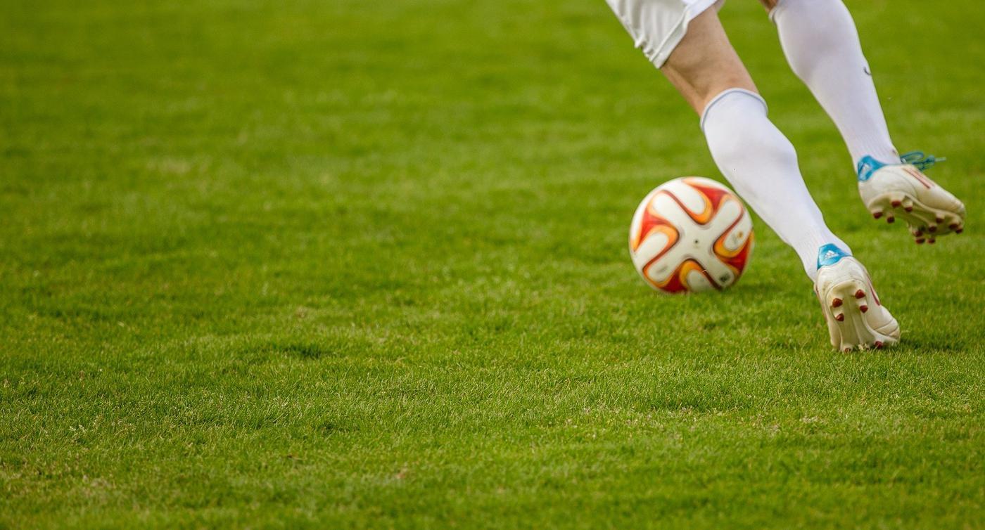 Ein Spieler dribbelt einen Fußball.