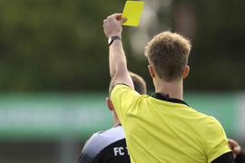 Ein Schiedsrichter zeigt die Gelbe Karte