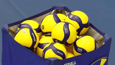Volleybälle liegen in einem Korb.