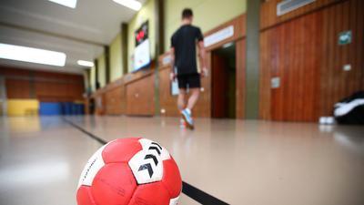 Warten auf die Wiederaufnahme des Trainings- und Spielbetriebs: Ein Handball liegt auf dem Spielfeld, während im Hintergrund ein Handballspieler die Halle verlässt