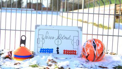 Am Zaun des wegen des Lockdowns geschlossenen Sportplatz liegen Hütchen, Eine Taktiktafel und ein Ball. Wegen des Shutdowns droht dem Amateurfußball in Deutschland erneut ein Saisonabbruch.