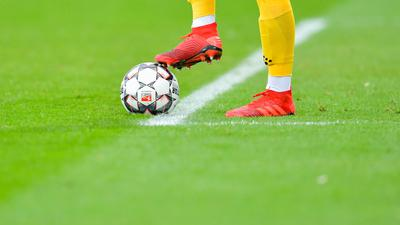 Ein Fußballer kickt den Ball.