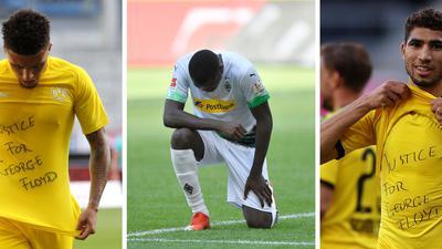 """Dortmunds Jadon Sancho (l) trägt ein Trikot mit der Aufschrift """"Justice for George Floyd"""", Der Gladbacher Marcus Thuram kniet auf dem Rasen."""