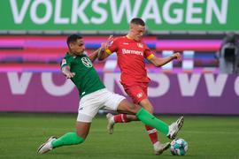 Wolfsburgs Neuzugang Maxence Lacroix (l) setzt gegen Leverkusens Talent Florian Wirtz zur Grätsche an.