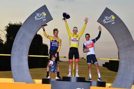Der Zweitplatzierte Primoz Roglic (l-r) (mit seinem Sohn Lev), Tour-Sieger Tadej Pogacar und der Drittplatzierte Richie Porte feiern auf dem Podium.