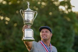 Der muskulöse Golfer Bryson DeChambeau aus den USA hält nach dem Sieg der US Open seine Trophäe in die Höhe.