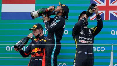 Auf dem Podest genehmigen sich der Zweitplatzierte Max Verstappen (l-r), Sieger Lewis Hamilton und Daniel Ricciardo zunächst einen großen Schluck.