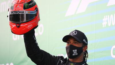 Lewis Hamilton feiert mit dem Helm von Michael Schumacher den Sieg auf dem Nürburgring.