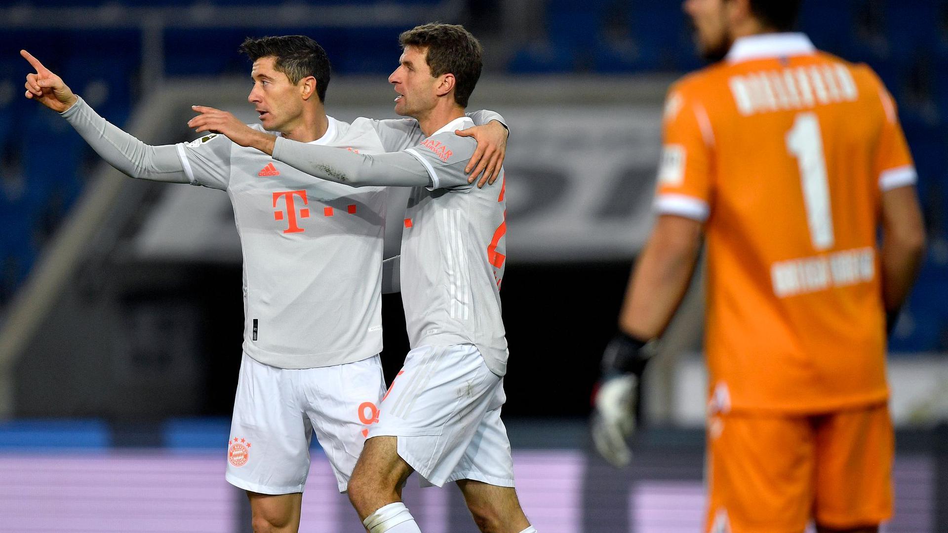 Bayerns Robert Lewandowski (l) und Thomas Müller bejubeln Müller's Tor zur Führung.