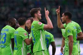 Wolfsburgs Wout Weghorst (M) bejubelt sein Tor zum 1:0 gegen Arminia Bielefeld mit Mannschaftskamerad Maxence Lacroix (r).