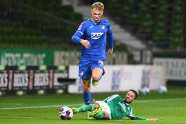 Werders Leonardo Bittencourt (r) versucht Hoffenheims Stefan Posch per Grätsche zu stoppen.
