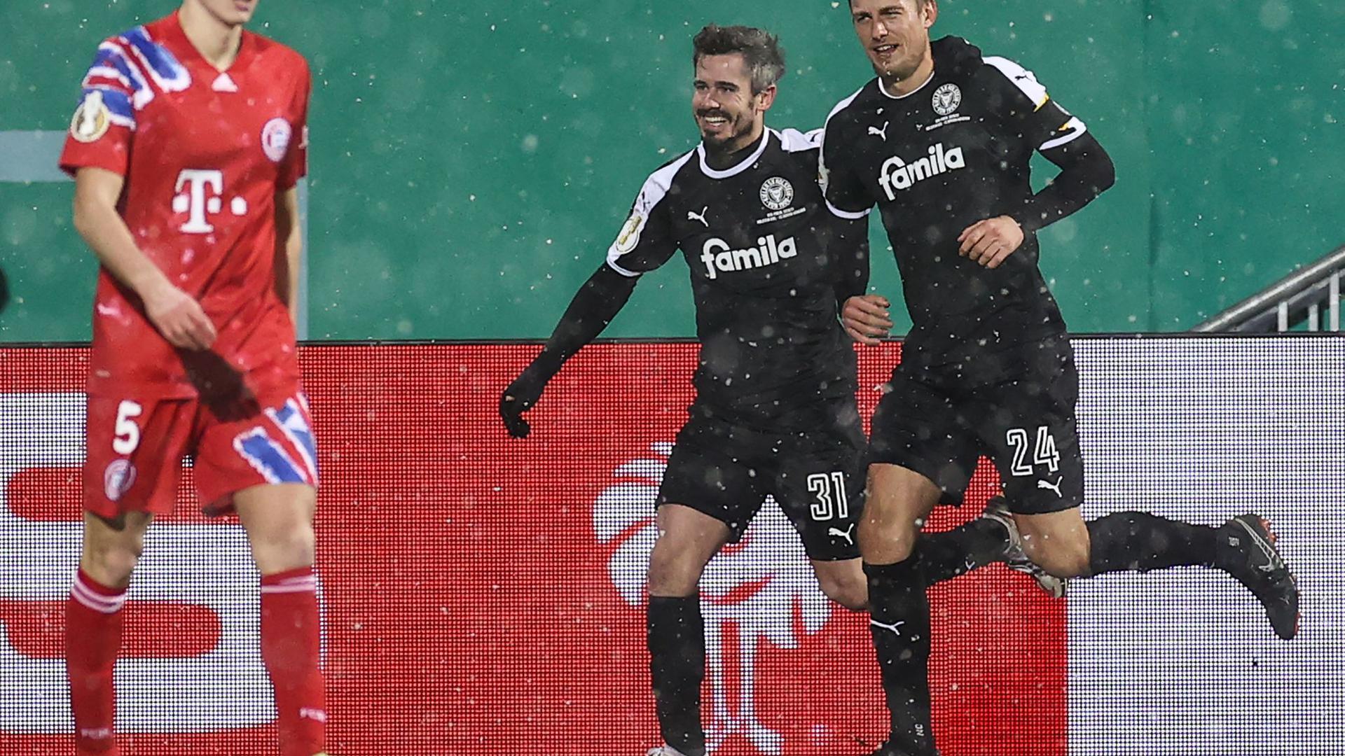 Der FCBayern München um Benjamin Pavard (l) verlor bei Holstein Kiel.