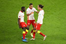 Leipzigs Yussuf Poulsen (r) bejubelt sein Tor zum zwischenzeitlichen 2:2 mit Dayot Upamecano (l) und Tyler Adams.