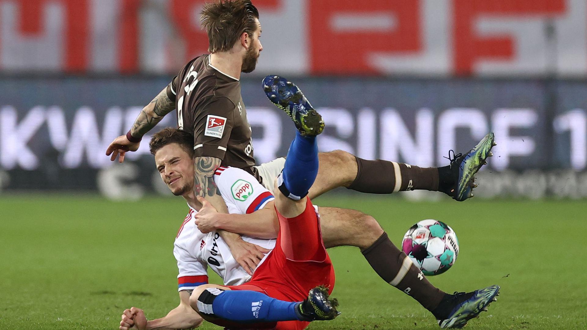 Moritz Heyer (l) vom HSV und Guido Burgstaller vom FC St. Pauli kämpfen um den Ball.
