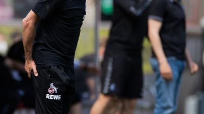 Kölns Trainer Friedhelm Funkel versucht seine Spieler auf dem Platz zu erreichen - im Hintergrund steht Freiburgs Trainer Christian Streich.