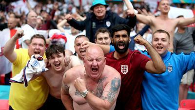 Englische Fußballfans feiern den Sieg gegen Deutschland - Schulter an Schulter - im Wembley Stadion.