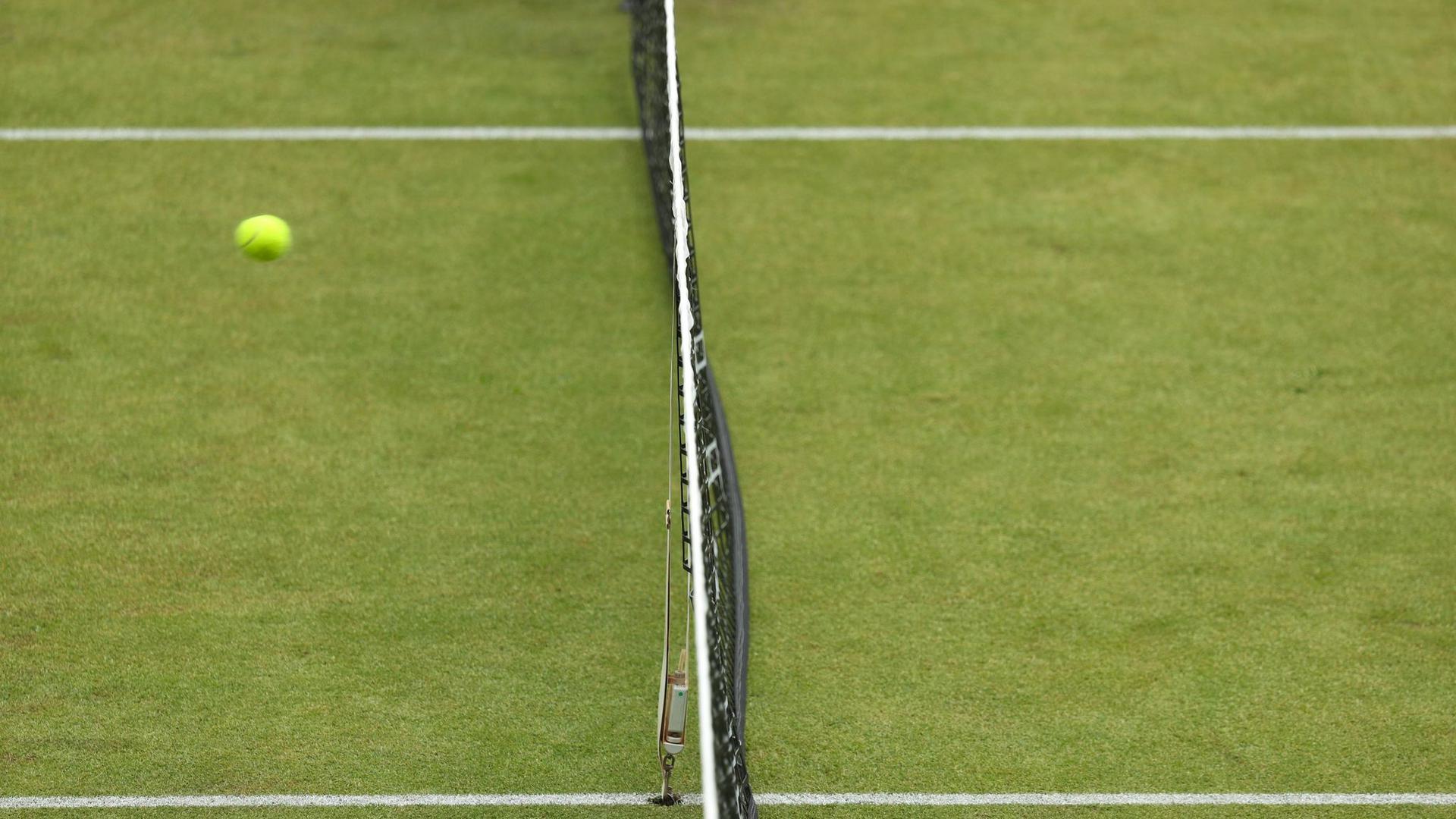 Ein Tennisball fliegt über das Netz.