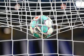Ein Fußball liegt vor der Partie im Netz.