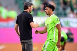 Wolfsburgs Trainer Mark van Bommel klatscht nach der Pokalpartie gegen Preußen Münster mit Omar Marmoush ab.