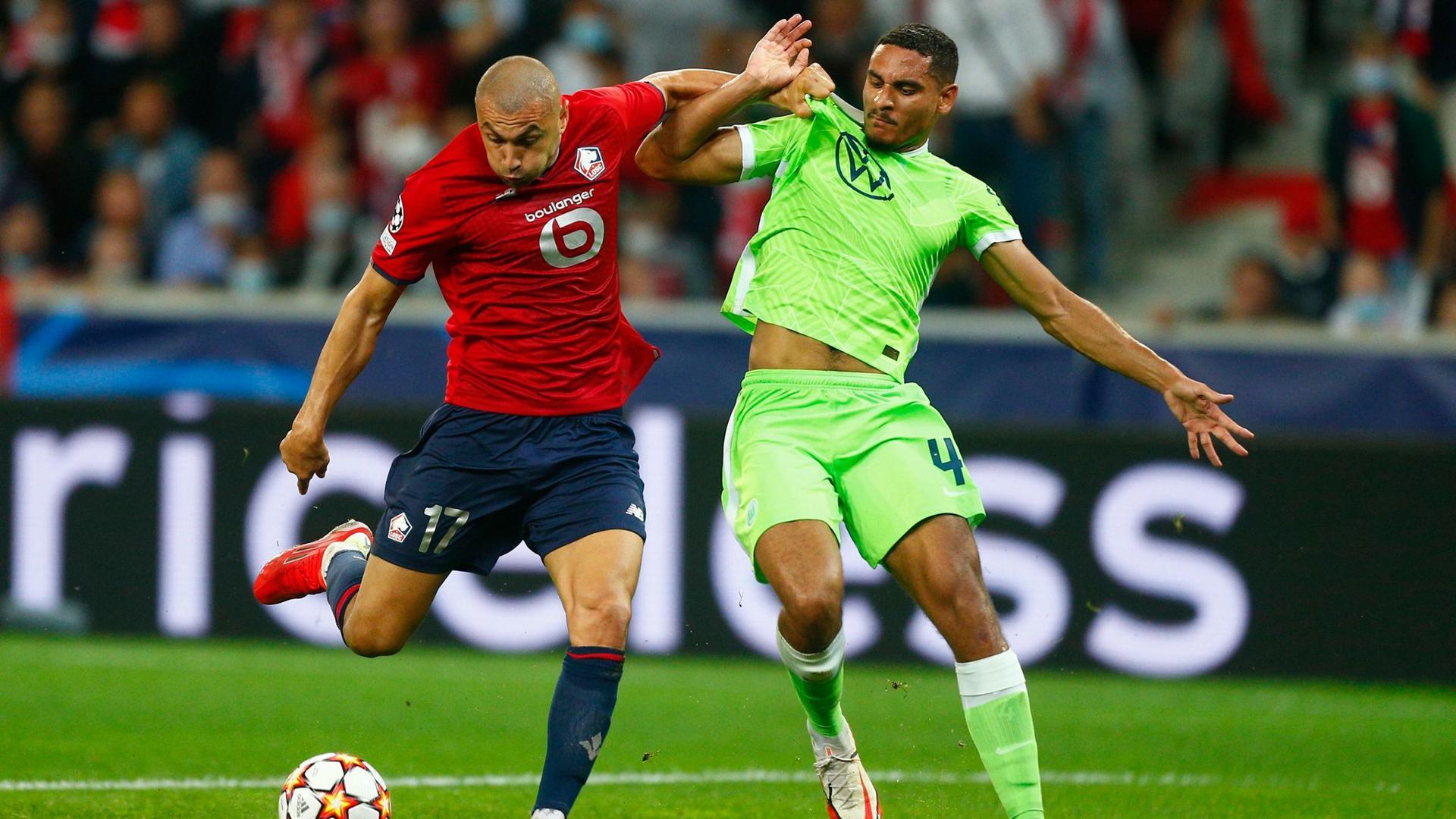 Maxence Lacroix vom VfL Wolfsburg (r) kann sich im Kampf um den Ball nicht gegen Burak Yilmaz vom OSC Lille durchsetzen.