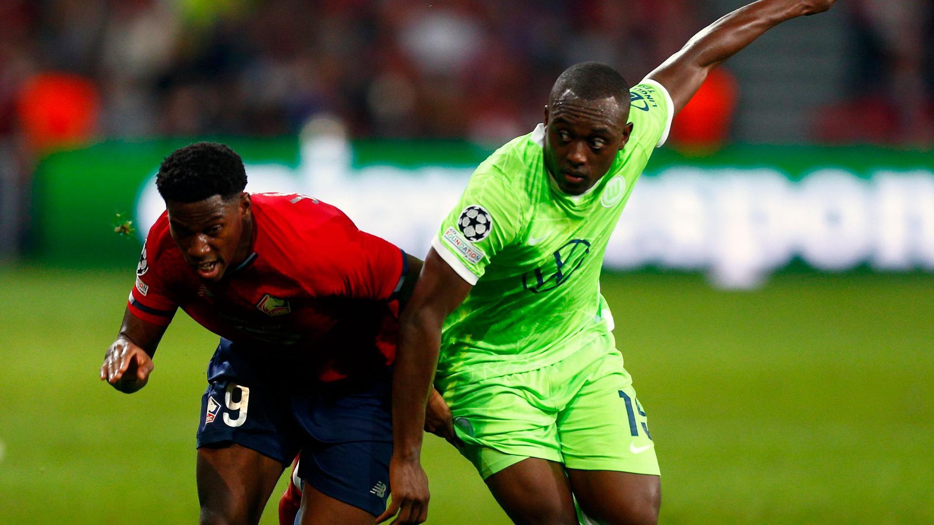 Jonathan David (l) vom OSC Lille gegen Kevin Mbabu vom VfL Wolfsburg.