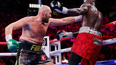 Tyson Fury (l) trifft Deontay Wilder mit seiner Linken.