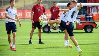 Bayerns Joshua Kimmich (r), Leroy Sane (hinten)und Thomas Müller halten den Ball hoch. Co-Trainer Dino Toppmöller beobachtet das Warm-Up.