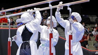 Mitglieder des Organisationsteams desinfizieren in Schutzanzügen und mit Mund-Nasen-Schutz die Geräte.