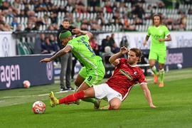 Wolfsburgs Aster Vranckx (l) spielt gegen Freiburgs Lucas Höler.