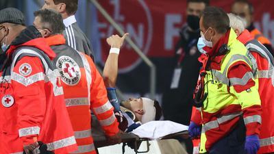 Der Nürnberger Tom Krauß (M) wird verletzt aus dem Stadion getragen, zeigt aber mit dem Daumen nach oben.