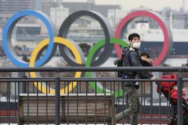 Olympia-Vorfreude? Nicht so sehr in Tokio. Das Bild zeigt einen Mann mit einer Gesichtsmaske und seinen Kindern vor dem Hintergrund der Olympischen Ringe.